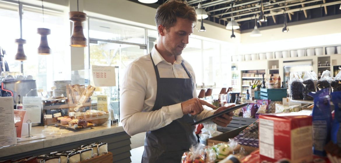 Employee In Delicatessen Checking Stock With Digital Tablet