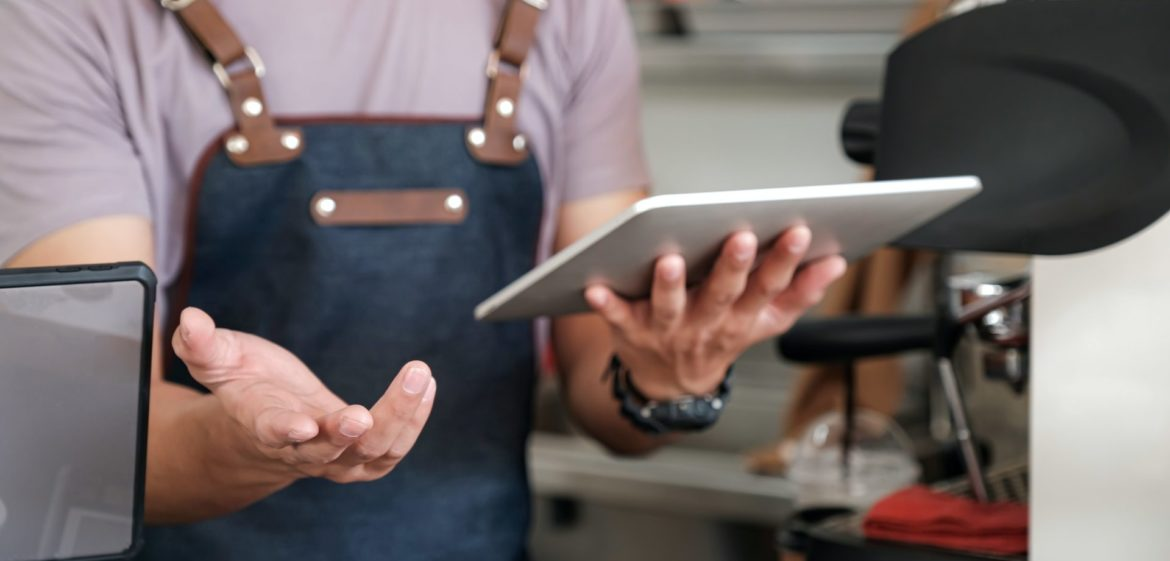 barista holding a tablet in hand, recommending menu and receiving orders from customers.