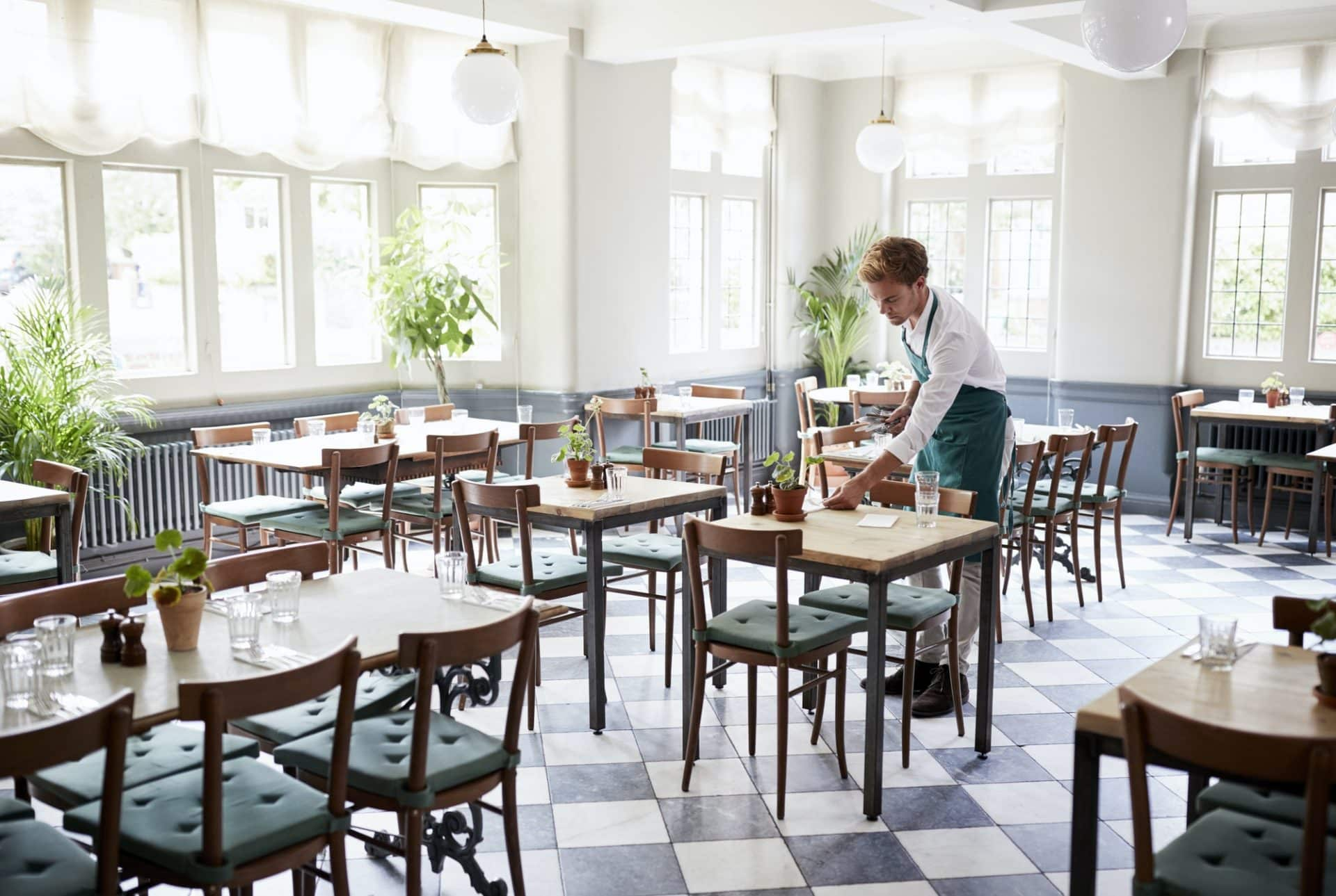 Waiter Laying Tables In Empty Restaurant